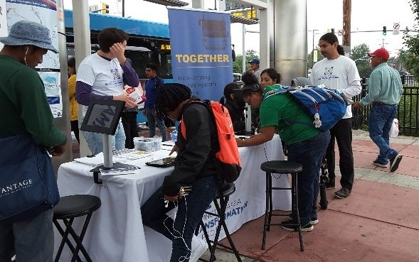 This picture shows people filling out surveys via tablets at a pop-up event outside of a bus station.