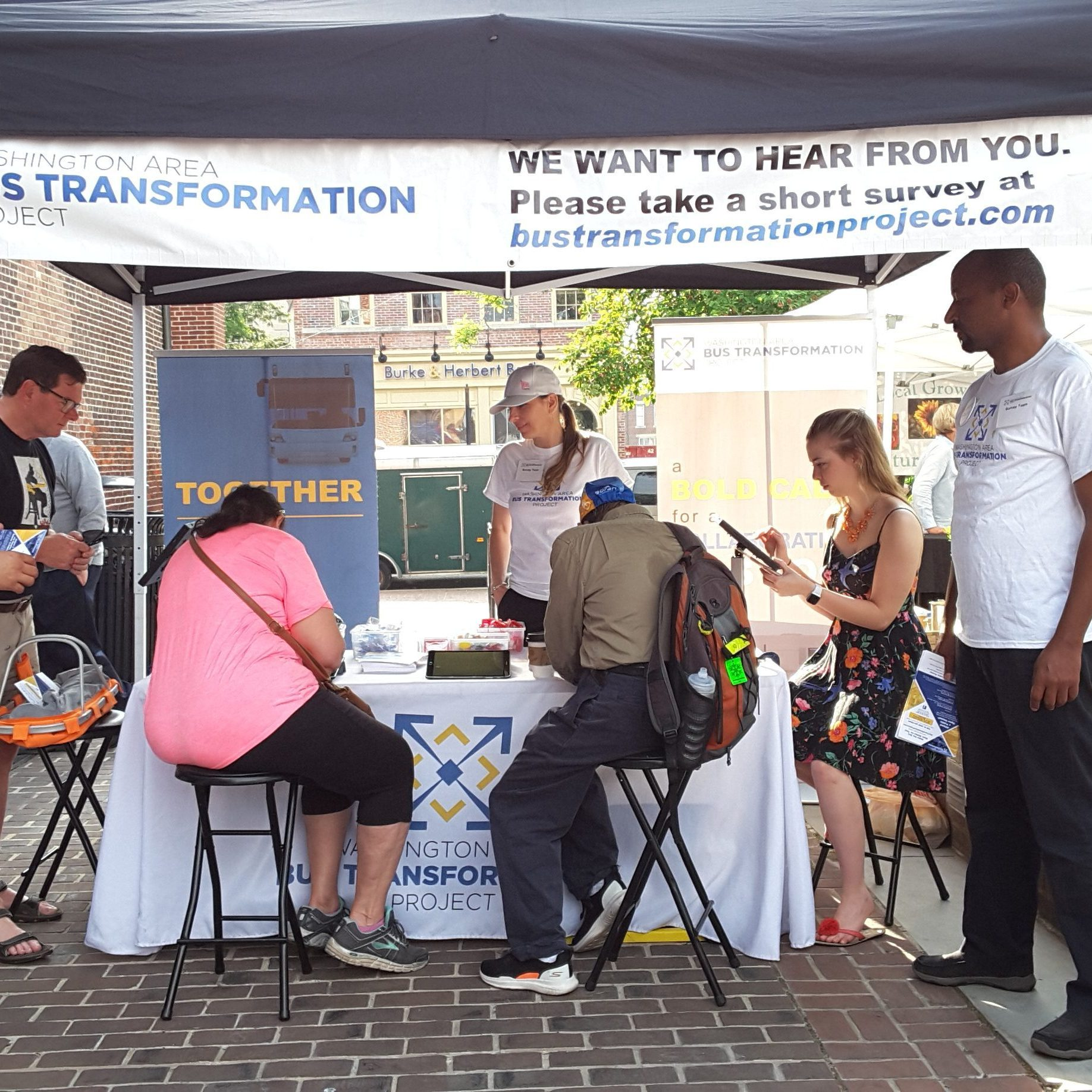 People gathered at the old town farmers market popup event booth